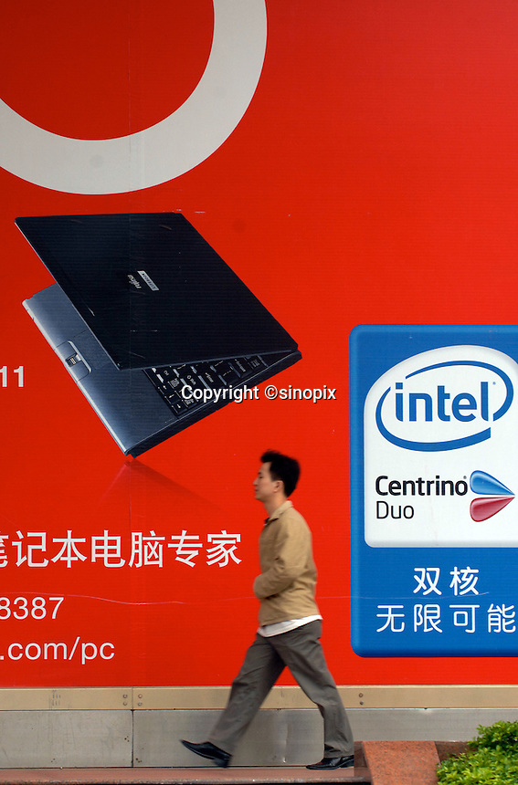 People pass an advert fro Fujitsu and Intel computers at a computer shopping mall in the Tien He District of Guangzhou, China.                                                                                                                          .