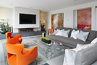 The spacious sitting room has a plasma screen set in a recess above the slate fireplace. Sliding doors lead to a cosy family television room to one side. The sitting area which consists of two large grey family sofas and a glass coffee table that sit on an area rug. A pair of orange chairs punctuate the sitting area and add colour and fun to the space.