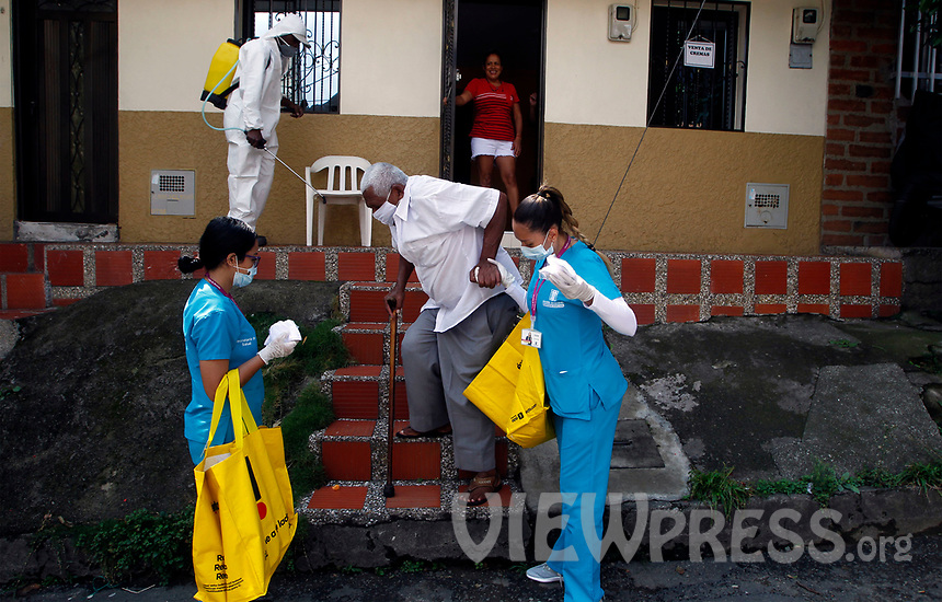 MEDELLIN, COLOMBIA- MAY 29: Two nurses help a man, in the neighborhood of Santa Cruz in Medellín, Colombia, on May 29, 2020. The mayor of Medellín and the private company offer a mask facial, antibacterial gel and alcohol for city communes As a preventive measure against the new coronavirus COVID-19. (Photo by Fredy Builes / VIEWpress via Getty Images)