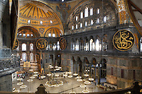 High angle view of interior and domes, with the mirhab below, Hagia Sophia, 532-37, by Isidore of Miletus and Anthemius of Tralles, Istanbul, Turkey. Hagia Sophia, The Church of the Holy Wisdom, has been a  Byzantine church and an Ottoman mosque and is now a museum. The current building, the third on the site, commissioned by Emperor Justinian I, is a very fine example of Byzantine architecture. The historical areas of the city were declared a UNESCO World Heritage Site in 1985. Picture by Manuel Cohen.