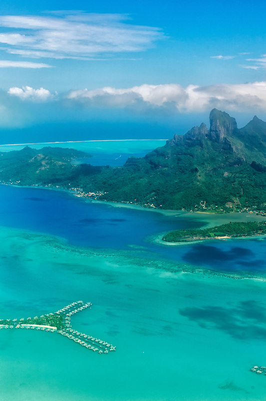 View of Bora Bora from the air with bungalows over water and Mt Otemanu. French Polynesia