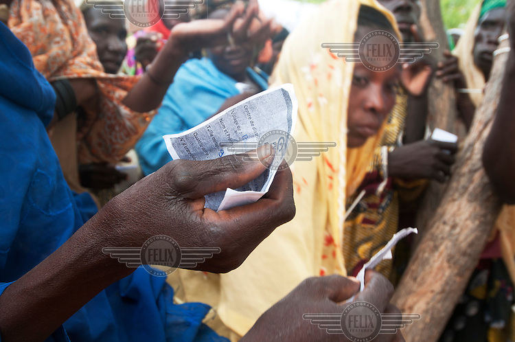 People hold food aid distribution tickets as they await their allowance at a distribution centre in Dosso. A drought in southern Niger has affected up to 8 million people.