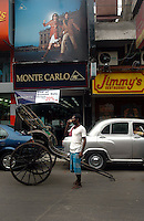 A rickshawpuller having tea in front of a Monte Carlo showroom in  Kolkata, West Bengal,  India  7/18/2007.  Arindam Mukherjee/Landov