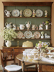 Dining room with round wooden table set for tea in front of green painted dresser and collection of china.