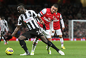 29.12.2012. North London, England. ..Cheick Tiote of Newcastle United holds off Alex Oxlade-Chamberlain of Arsenal during the Premier League game between Arsenal and Newcastle United from Emirates Stadium