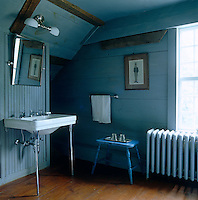 The wooden walls of an attic bathroom have been painted a flat slate blue for a fresh yet cosy feel
