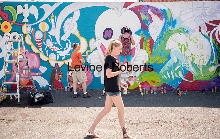 A visitor walks past work at the Welling Court Mural Project in the Astoria neighborhood of Queens in New York on Saturday, June 13, 2015. The annual neighborhood event decorates walls in this industrial part of Astoria. The project is crowd-funded and emerging street artists work side by side with established stars.  (© Richard B. Levine)