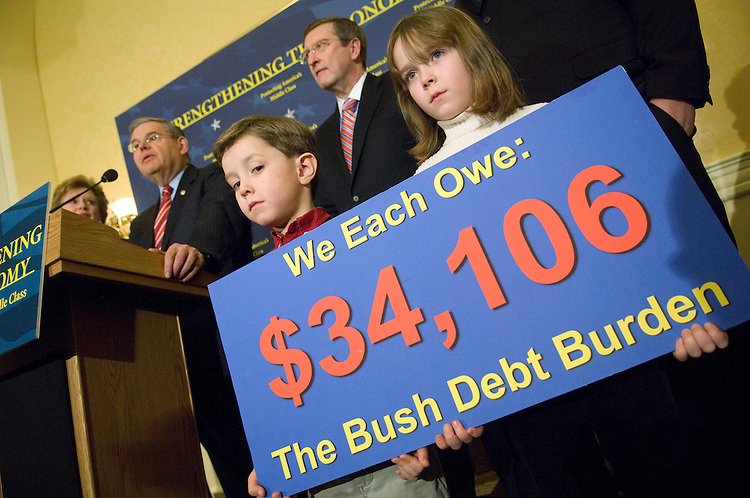 WASHINGTON, DC - Feb. 12: William Thorne, 5, and sister Caroline, 6, hold a sign during a news conference with Senate Budget Chairman Kent Conrad, D-N.D., behind the children, Senate Democrat Steering & Outreach Committee Chairwoman Debbie Stabenow, D-Mich., far left background, and Sen. Robert Menendez, D-N.J., speaking, on the impact of the president's proposed budget. Cecily Thorne of Silver Spring, Md., the children's mother, said they are related to a member of Conrad's staff. (Photo by Scott J. Ferrell/Congressional Quarterly)