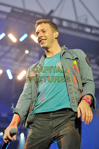 Chris Martin of Coldplay .performing live in concert at the Emirates Stadium, London, England, UK,.1st June 2012..music gig on stage half length turquoise paint splattered t-shirt denim jacket jeans microphone .CAP/MAR.© Martin Harris/Capital Pictures.