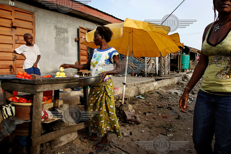 A woman sells oranges in the Ajegunle slum.