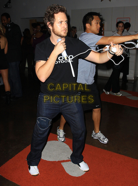 A.J. BUCKLEY.Active For Life event and auction to benefit the March of Dimes Inside held At The Warner Drive Studio, Culver City, California, USA..January 8th, 2009.video game gesture action sport full length funny black top jeans denim arms punch punching fists profile aj .CAP/ADM/KB.©Kevan Brooks/AdMedia/Capital Pictures.