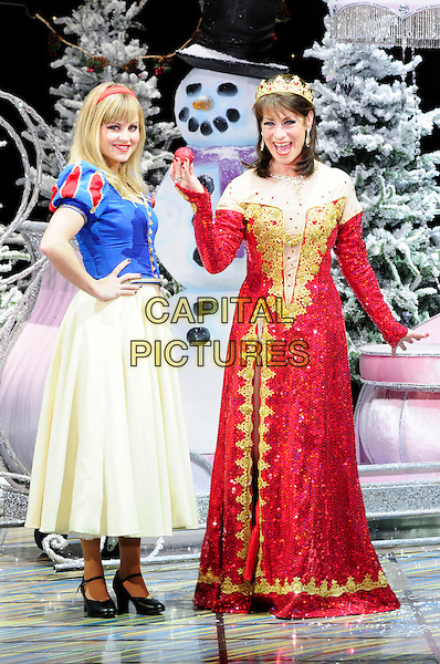 TINA O'BRIEN & DINA PAYNE.First Family Entertainment theatre company's annual group Pantomime photocall at Piccadilly Theatre, London, England..November 26th, 2010.stage costume panto pantomime full length red yellow blue dress snow white crown queen apple mouth open side.CAP/CAS.©Bob Cass/Capital Pictures.