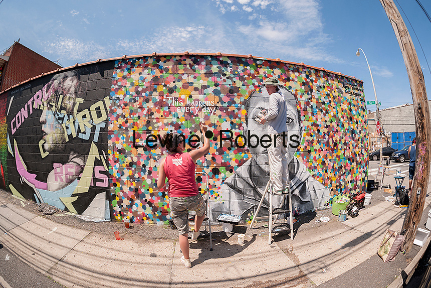 Street artists Katie Yamasaki and Caleb Neelon at work on their rmural at the Welling Court Mural Project in the Astoria neighborhood of Queens in New York on Saturday, June 13, 2015. The annual neighborhood event decorates walls in this industrial part of Astoria. The project is crowd-funded and emerging street artists work side by side with established stars.  (©Richard B. Levine)