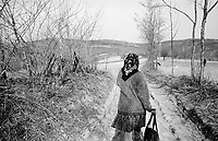 ROMANIA / Maramures / Valeni / April 2003..Maria, 22, returns from the weekly market to join her parents who are planting potatoes above the village...© Davin Ellicson / Anzenberger...