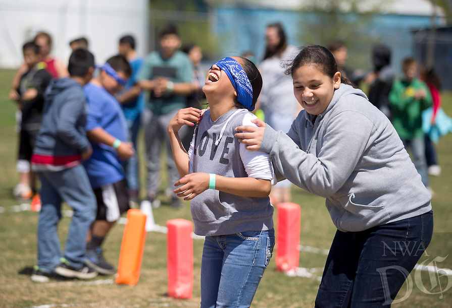 NWA Democrat-Gazette/JASON IVESTER<br /> Karrelys (cq) Cardona (right), Decatur sixth-grader, helps guide Daisy Alonso, fifth-grader, through a blindfolded maze Wednesday, April 12, 2017, on the Decatur football field. A group of Decatur eighth-graders organized the event, Revolution 2021, for Decatur Middle School students.