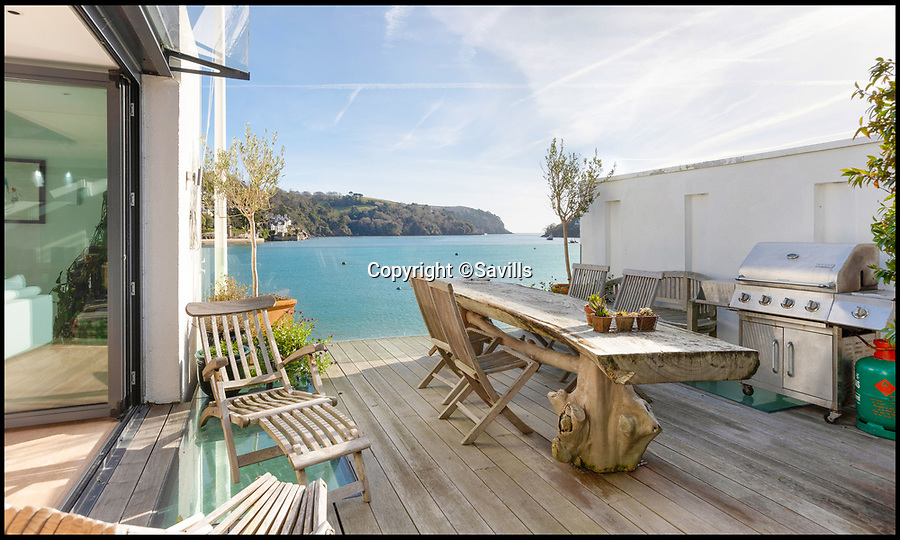 BNPS.co.uk (01202 558833)<br /> Pic: Savills/BNPS<br /> <br /> Alfresco dining with lots of seaside air.<br /> <br /> An award-winning waterfront home that has spectacular seaside views has gone on the market for £5m.<br /> <br /> The aptly named River House sits right on the Dart Estuary in Devon and has been so cleverly designed there is a glass floor in the master bedroom that looks down on the water.<br /> <br /> Its main living areas have floor-to-ceiling bi-fold doors and glass Juliet balconies to give the property a feel of Venice rather than Devon.<br /> <br /> Interestingly, the five bedroom house is being sold along with a nearby two bedroom town house that is owned by the same vendors.