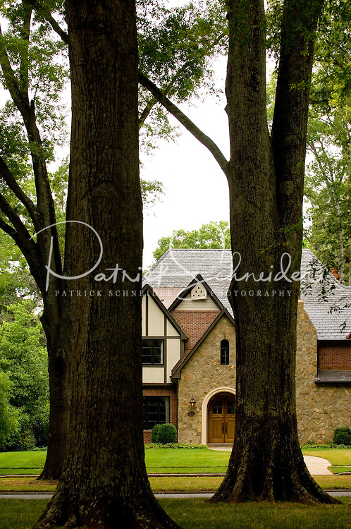 A home is in view through the large oak trees in the Myers Park neighborhood in Charlotte, NC. Myers Park is one of the premier neighborhoods in North America and known for its large canopy of trees.