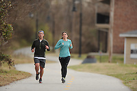 NWA Media/ANDY SHUPE - Max Mahler, left, and fiancée Lydia McCain run south on the Scull Creek Trail, a section of the Northwest Arkansas Razorback Greenway, Sunday, Dec. 21, 2014, in Fayetteville. The greenway is a regional trail system that connects Northwest Arkansas.