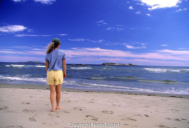 Woman stands on Seawall Beach in Phippsburg, Maine and looks out over the Atlantic Ocean