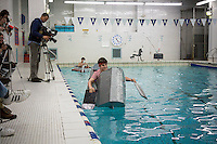 """Jack Killcoyne, a junior, pilots his team's boat in the Brooklyn Technical High School Cardboard Boat Regatta in the school's pool in Brooklyn in New York on Friday, March 1, 2013. As part of Engineering Week the teams of students constructed boats made only of cardboard and duct tape. The team's assigned """"captain"""" piloted their boat from one end of the pool to the other and back in a heat with other boats, hopefully without sinking. The surviving boats were timed and the winners received bragging rights with an award also going to the most spectacular sinking. (© Richard B. Levine)"""