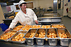 Hospital Assistant Chef sorting roast potatoes into containers in preparation for ward hot trolleys,