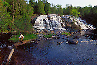 A trout fisherman casts with a fly rod while carrying a spinning rod at Bond Falls on the Ontonagon River near Paulding, Michigan.