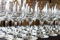 Many empty wine glasses are lined up on black table cloth ready to be used for wine tasting or large event.