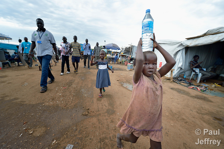 A girl carries water inside a camp for internally displaced families located inside a United Nations base in Juba, South Sudan. The camp holds Nuer families who took refuge there in December 2013 after a political dispute within the country's ruling party quickly fractured the young nation along ethnic and tribal lines. The ACT Alliance is providing a variety of services, including fresh water, sanitation and refuse collection services, to the more than 20,000 people living in the camp.