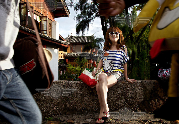 A visitor smiles while she sits on a bridge in Lijiang a town whose historic buildings are a major tourist attraction and an UNESCO World Heritage Site. /Felix Features