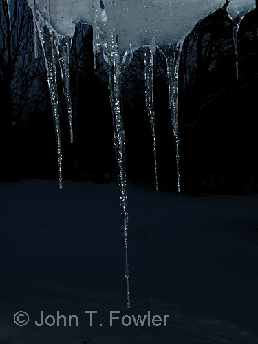 Icicles hanging from eaves of roof<br />