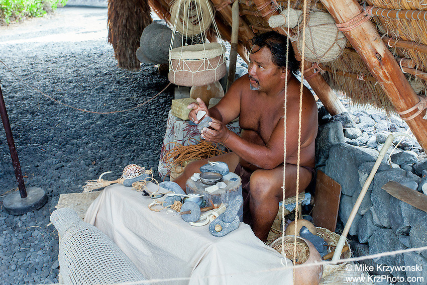 Native Hawaiian man holding artifacts while giving Hawaiian culture lecture in Pu'uhonua o Honaunau place of refuge national historical park, Big Island, Hawaii
