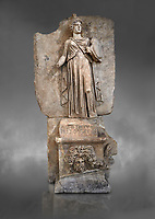 Roman Sebasteion relief sculpture personifing a Balkan Warrior  Aphrodisias Museum, Aphrodisias, Turkey.  Against a grey background.<br /> <br /> The relief figure personifies a Balkan Warrior tribe defeated by Tiberius in AD 6-8 before he became emperor. She wears a classical dress, cloak and helmet and carries a small shield and probably once a spear. A builder&rsquo;s inscription, &ldquo;Pirouston&rdquo;, written above the shield, ensured the relief was put on the right base