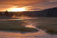 The Madison River flows with warm warmed from thermal features and appears to smoke as it reaches cool autumn air, Yellowstone National Park, Wyoming