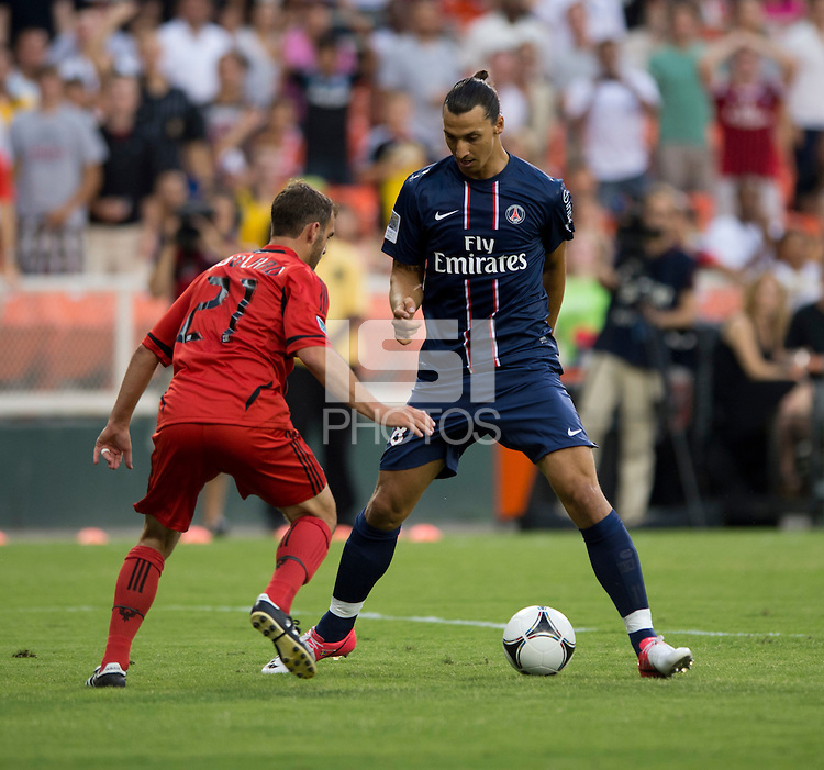 Zlatan Ibrahimovic (18) of Paris Saint-Germain FC looks to move past Daniel Woolard (21) of D.C. United during the game at RFK Stadium in Washington, DC.  Paris Saint-Germain FC tied D.C. United, 1-1.