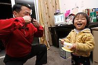 Li Fang (gauche) explique à sa petite-fille Li Siqi (droite) qu'il faut rapprocher son bol pour manger son riz avec des baguettes. L'enfant, qui se sert pour une des premières fois de sa vie de baguettes, s'exclaffe devant le mime du grand-père, à Baoshan, près de Shanghai, le 10 mai 2008. Photo par Lucas Schifres/Pictobank