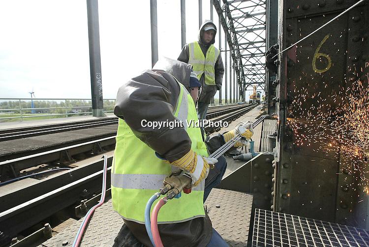 """Foto: VidiPhoto..OOSTERBEEK - Het treinverkeer tussen Arnhem en Nijmegen ligt dit weekend stil wegens het vernieuwen van stukken rijkdek op de spoorbrug over de Rijn, het afgraven van de spoordijk, het slaan van stalen pijlers en het aanbrengen van brugdelen. De spoordijk bij Oosterbeek wordt afgegraven in het kader van het project """"Ruimte voor Rivieren"""". De dijk verdwijnt en maakt plaats voor een spoorbrug. Vanaf maandag rijden de treinen weer."""