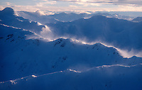 High winds blow snow off the ridges of the coastal mountains of southeast Alaska.