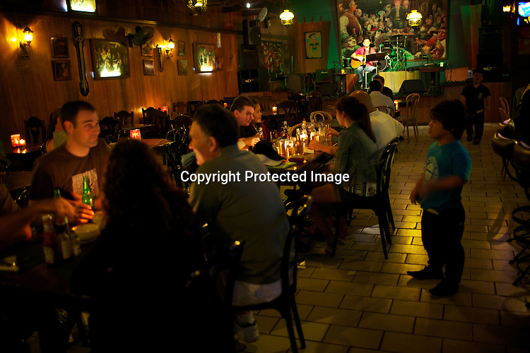 "Guests enjoy their dinner while a performer sings on the stage of the Hobbit House in Makate, Manila in Philippines. The restaurant/bar is entirely staffed by ""little people.""  Photo: Sanjit Das"
