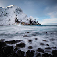 Winter mountain peaks rise over Bunes beach, Moskenesøy, Lofoten Islands, Norway