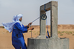 Moroccan man dressed in a traditional gandora at a well in the Sahara desert.