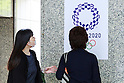 People look at the Tokyo 2020 Olympic Games logo on display at the Tokyo Metropolitan building on April 27, 2016, Tokyo, Japan. After scraping the original design last year due to accusations of plagiarism; The Tokyo 2020 Logo Selection Committee settled this week on a simple indigo-and-white checkered circle design by Asao Tokolo as a new emblem for the 2020 Summer Olympic Games. The final decision was announced on Monday 25th April after the selection committee had checked through almost 15,000 design proposals. The new logos are already starting to appear on Tokyo 2020 related communications. (Photo by Rodrigo Reyes Marin/AFLO)