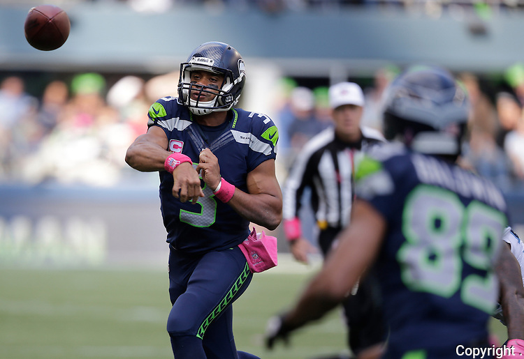 Seattle Seahawks quarterback Russell wilson, left, throws a pass to wide receiver Doug Baldwin (89) for a first down against the Tennessee Titans in the third quarter at CenturyLink Field in Seattle, Washington on  October13, 2013.  Wilson completed 23 passes for 257 yards and rushed 61 yards in the Seahawks 20-13 win over the Titians.    ©2013. Jim Bryant Photo. All Rights Reserved.