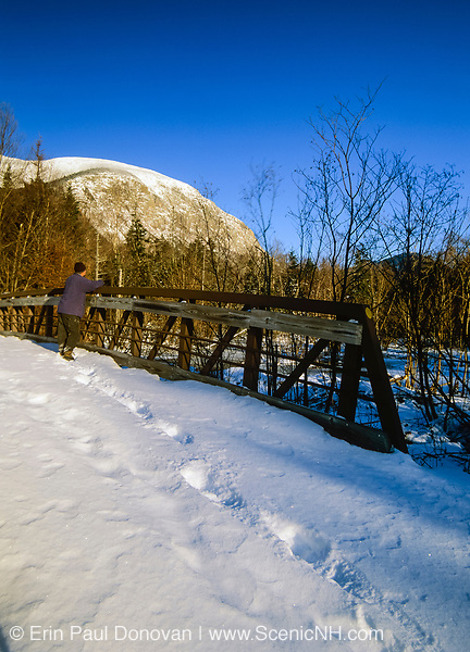 A hiker looking at the view from a bridge on Franconia bike path with Cannon Mountain in the background during the winter. Located in Franconia Notch, which is in the White Mountain National Forest of New Hampshire, USA.