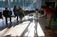 NWA Democrat-Gazette/CHARLIE KAIJO Chris Gorrie of Springfield Mo. (from right) shows Emma Gorrie 5, how to hula-hoop during the Noon Year's Eve event on Sunday, December 31, 2017 at Crystal Bridges in Bentonville. Visitors rang in the New Year (without staying up past bedtime) at the third annual family celebration including arts projects, performances and a family dance party.