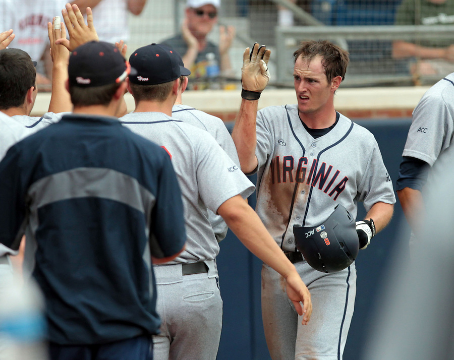 Virginia catcher Robbie Coman (8), right, celebrates his score with teammates in the third inning of an NCAA college baseball tournament super regional game against Maryland in Charlottesville, Va., Sunday, June 8, 2014.  (AP Photo/Andrew Shurtleff)