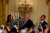Israeli President Reuven Rivlin lights the menorah during a Hanukkah reception in the East room of the White House while US President Barack Obama, US First Lady Michelle Obama (L) and Nechama Rivlin, the wife of Reuven Rivlin (2L) watch, at the White House, in Washington, DC, December 9, 2015.  <br /> Credit: Aude Guerrucci / Pool via CNP