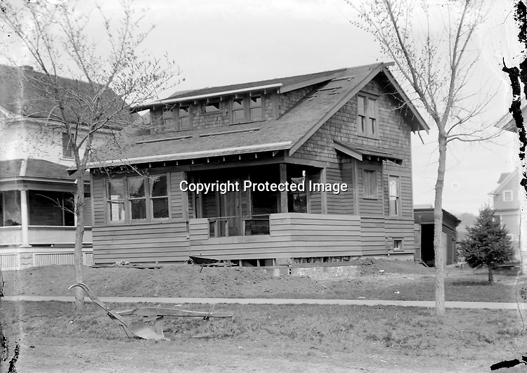 A NEW BUNGALOW. This craftsman-style bungalow appears to be nearing completion, but unfortunately the address has not yet been affixed to the house. The era of these photographs, roughly 1910 to 1925, coincides with the introduction of bungalows among Lincoln house types and their time of greatest popularity. The plow in front of the house probably was used at the construction site to break the soil before the basement was scooped with a horse-drawn drag.<br /> <br /> Photographs taken on black and white glass negatives by African American photographer(s) John Johnson and Earl McWilliams from 1910 to 1925 in Lincoln, Nebraska. Douglas Keister has 280 5x7 glass negatives taken by these photographers. Larger scans available on request.
