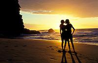 Silhouette of couple kissing on Kalalau Beach, Kauai with a golden sunset behind them