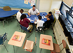 (09/18/17 Springfield MA)  Math teacher Evan Christensen works with seventh grade students during a math game on negative and positive numbers, in his classroom at John J. Duggan Academy, Monday, Sept. 18, 2017, in Springfield. The students, from left, Tyshawn Heslope, Yasmine Badillo, Josue Ruiz and Christopher Marti.  Herald Photo by Jim Michaud