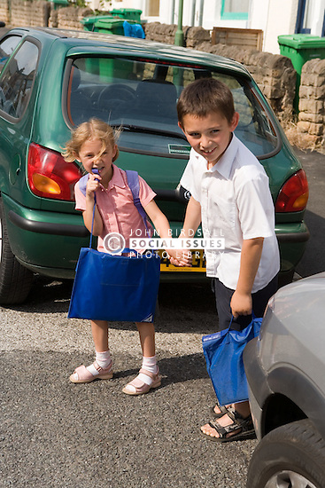 Brother and sister crossing the road in a dangerous place,